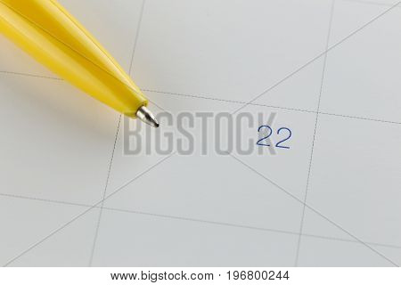 yellow pen points to the number 22 on calendar background in concept of appointment schedules and important dates.