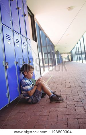 Side view of boy using mobile phone while sitting by lockers in corridor at school