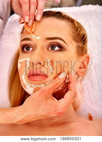 Collagen face mask. Facial skin treatment. Face of woman receiving cosmetic procedure in beauty salon close up number one isolated. Beautician removes mask. Healing clay to preserve youth.