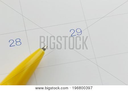 yellow pen points to the number 29 on calendar background in concept of appointment schedules and important dates.