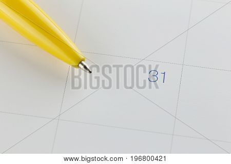 yellow pen points to the number 31 on calendar background in concept of appointment schedules and important dates.
