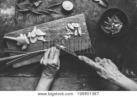 Aerial view of hands with knife cutting lemon grass
