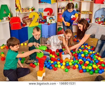 Children playing in kids cubes indoor. Lesson in primary school. Body part of girl and boy together play. Development of fine motor skills of the child's fingers.