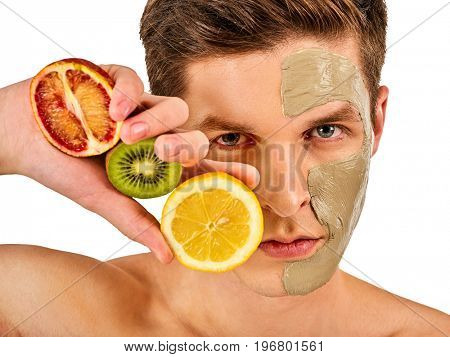 Facial mask from fresh fruits and clay for man concept. Face with treatment mud applied. Male holding grapefruit half for skin care procedure in salon. Cosmetic masks with natural ingredients.