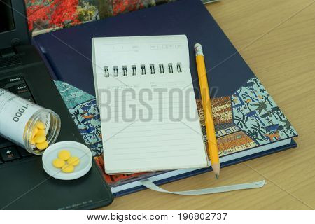 Notebook pencil pills in opened bottle and laptop on wooden table