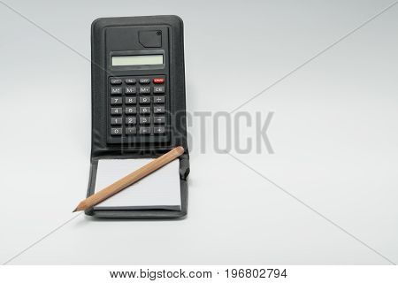 Pencil on the notebook and black calculator