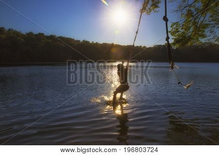boy jumping into the water by bungee. kid swings on a rope. Back view. The concept of healthy lifestyle