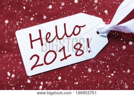 One White Label On A Red Textured Background. Tag With Ribbon And Snowflakes. English Text Hello 2018 For Happy New Year Greetings