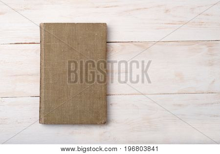 Top view of old book on wooden background