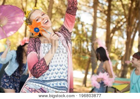 Portrait of happy woman holding pinwheel while enjoying at campsite