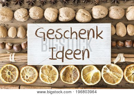 Sign With German Text Geschenk Ideen Means Gift Ideas. Christmas Food Flat Lay With Walnut, Hazelnut, Cinnamon Sticks And Orange Peel. Brown Wooden Background