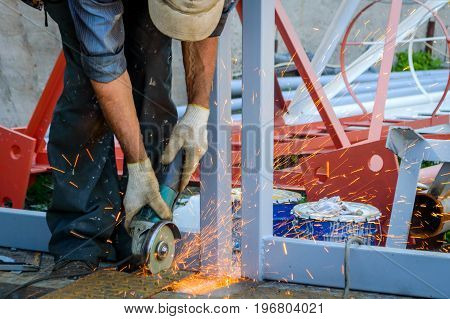 Worker using an angle grinder for cut of metall and producing a lot of sparks.