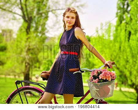 Bikes bicycle girl. Teenager girl wearing blue polka dots dress looking camera keeps bicycle with flowers basket. Lot of green tree and grass in park. Happy and free girl teenager on a green glade.