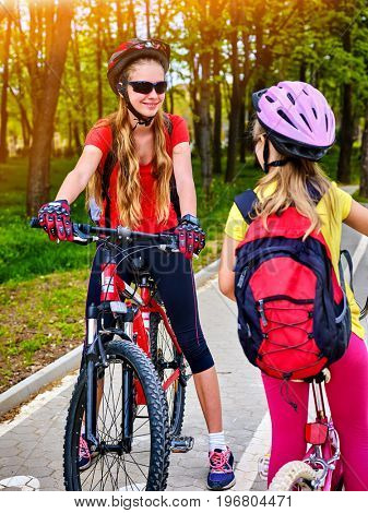 Bicycle path and sign with children. Girls wearing helmet with rucksack ciclyng ride. Kids are on white bike lane. Alternative to urban transport. Friendship between children of different ages.