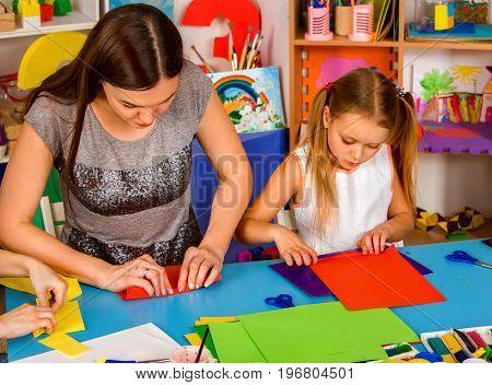 School children with scissors in kids hands cutting paper with teacher in class room. Children's project in kindergarten. Development of fine motor skills of fingers.