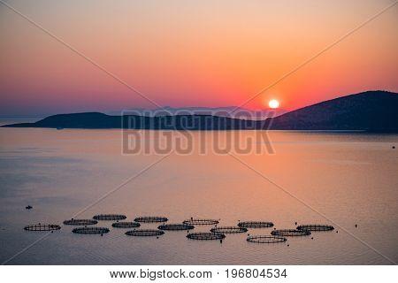Colorful sunrise over fish farm in sea, Greece