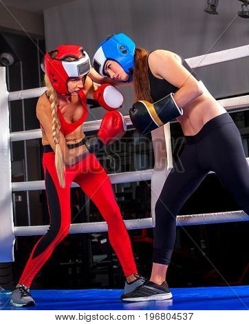 Two boxing women workout in fitness class. Sport exercise two female people .Boxer wearing red gloves to box and helmet in ring. Lower view angle. Couple female rivals in competition.