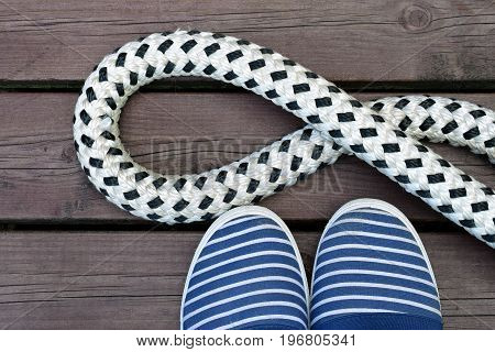 Sailor style shoes and rope on wooden deck.