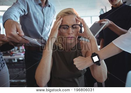Frustrated businesswoman sitting amidst team holding technologies at office