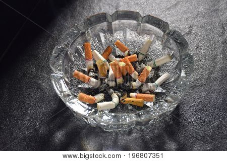 Many cigarette butts and ashes piled in an ashtray