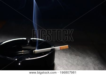 Lit cigarette with smoke lying on an empty black ashtray