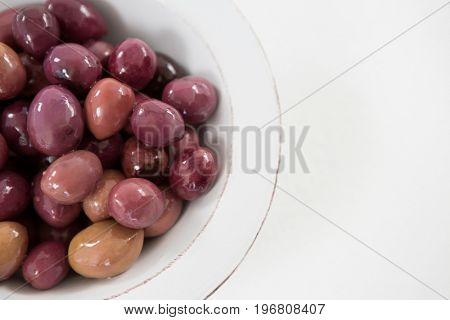 Close-up of marinated olives in white bowl