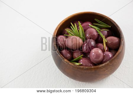 Pickled olives in wooden bowl on white background