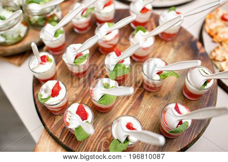 Pink coloured strawberry dessert in shot glass, decorated with mint leaves, on wood plate, several strawberries at background. catering buffet