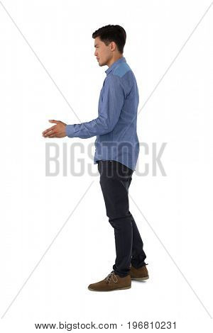 Side view of businessman extending arm for handshake while standing against white background
