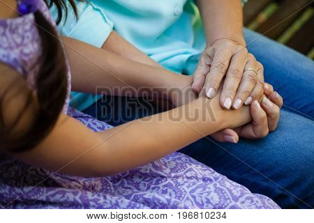 Midsection of senior woman holding hands of grandmother at backyard
