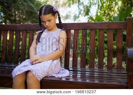 Upset girl looking down while sitting on wooden bench at garden