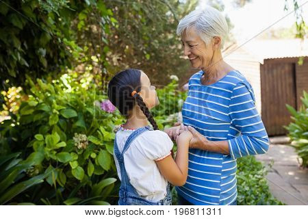 Smiling senior woman holding hands of granddaughter while standing against plants at backyard
