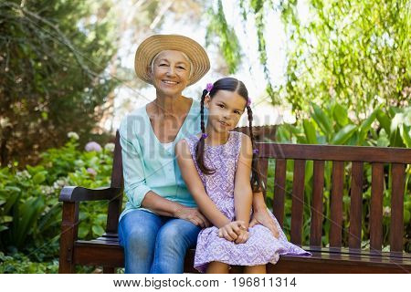Portrait of senior woman wearing hat sitting with granddaughter on wooden bench at backyard
