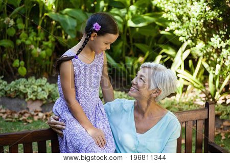Smiling senior woman looking at girl while sitting on wooden bench at backyard