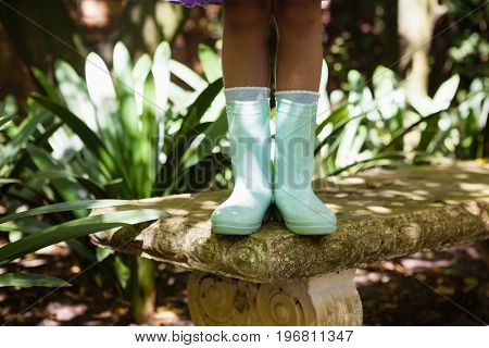 Low section of girl wearing green rubber boot standing on stone bench at backyard