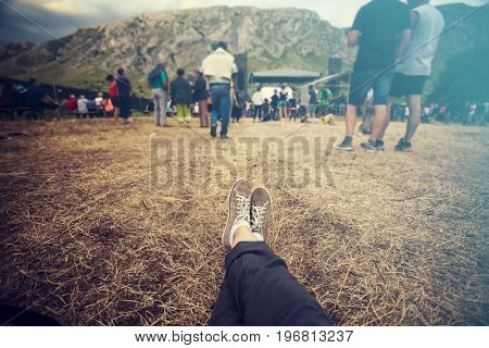 Teens at concert at summer festival. Legs of teenager at summer music festival, canvas shoes, sitting on the grass in front of stage