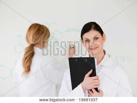 Scientist Writting A Formula Helped By Her Assistant