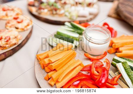 Fresh cucumber, carrot, red and green sweet paprika sliced in stripes on an olive wood cutting board on a grey abstract background. Step by step cooking. catering buffet