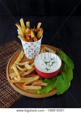 French fries in a paper cup with a white sauce