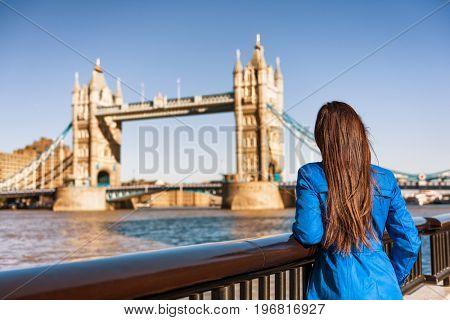 Tower Bridge London city travel woman tourist girl at Europe destination landmark famous attraction. Woman traveling in autumn season .