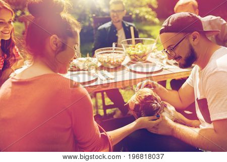 leisure, summer holidays, eating, people and food concept - happy friends with french bulldog dog having dinner at garden party