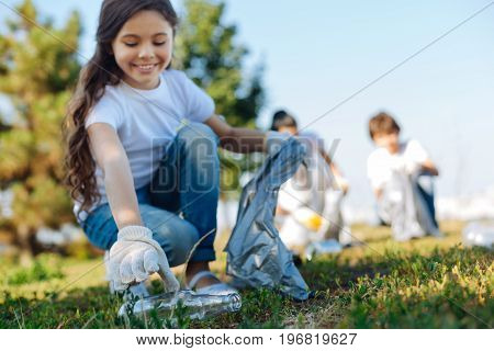 Sort all rubbish. Pleased kid looking at glass bottle while gathering garbage into package for rubbish and helping her friends in earth-cleaning