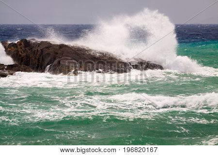 The wave crashed at rock in windy day.