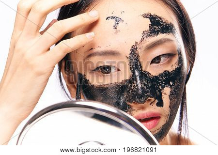 Beautiful young woman on white isolated background, black coal cosmetic face mask for face, asian.