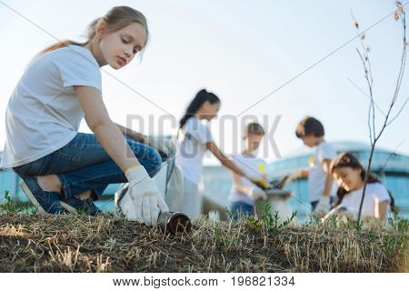 Make good more. Charming little lady being useful and trying for making nature in better condition while her friends planting trees