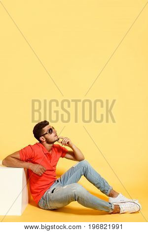 Handsome brunette guy sitting on floor in red shirt and jeans leaning on white cube looking up.