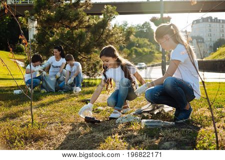 Cast out all the garbage. Responsible children cleaning yard, assembling rubbish and smiling