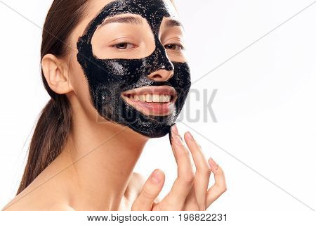 Beautiful young woman on white isolated background, black coal cosmetic face mask for face.