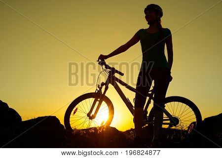 Silhouette of Young Woman Riding with Mountain Bike on the Summer Rocky Trail at Beautiful Sunset. Travel, Sports and Adventure Concept.