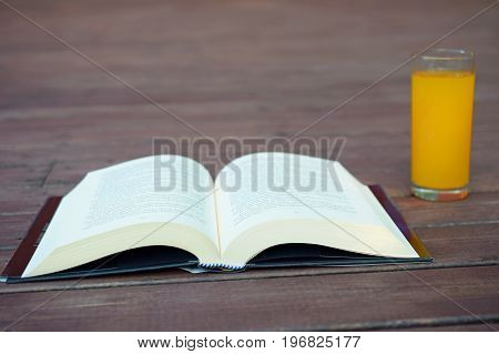 Open book and a yellow drink on brown wooden patio.